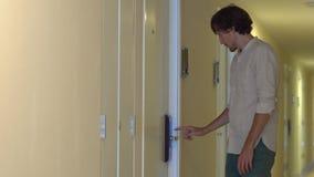 Den unga mannen kommer till hans lägenhet och öppnar ett elektroniskt lås genom att använda ett lösenord på en skärm arkivfilmer