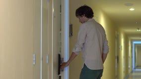 Den unga mannen kommer till hans lägenhet och öppnar ett elektroniskt lås genom att använda ett nyckel- kort lager videofilmer