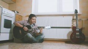 Den unga mannen komponerar musik på gitarren och spelar i köket, annat musikinstrument i förgrunden, Royaltyfria Bilder