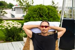 Den unga mannen kopplar av på stranddagdrivaren i solglasögon royaltyfri foto