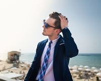 Den unga mannen korrigerar hans hår på bakgrunden av havet och himlen royaltyfri bild