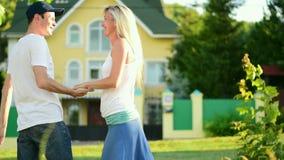 Den unga mannen kramar en kvinna och vänder henne i hans armar långsam rörelse