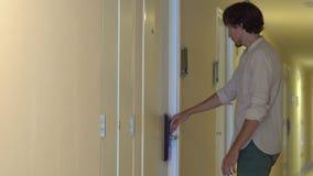 Den unga mannen lämnar hans lägenhet och stänger ett elektroniskt lås lager videofilmer