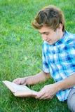 Den unga mannen läser en bok Arkivfoto