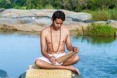 Den unga mannen läser forntida scripture royaltyfri bild
