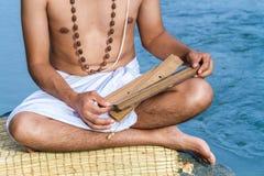 Den unga mannen läser forntida scripture royaltyfri foto