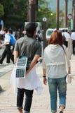 Den unga mannen laddar upp smartphonen, medan gå på gatan royaltyfria bilder