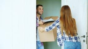 Den unga mannen levererar kartongen till kunden hemma Kvinnan undertecknar in skrivplattan för att motta jordlotten Arkivfoton