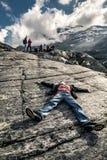 Den unga mannen ligger ner på stenen, Trollstigen, Norge Royaltyfri Fotografi