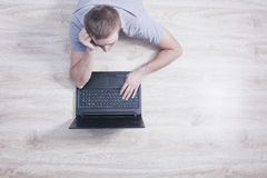 Den unga mannen ligger på golvet med en bärbar dator arkivfoton