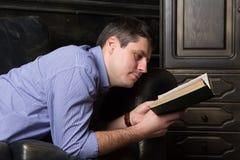 Den unga mannen ligger på soffan och läser en bok arkivbild