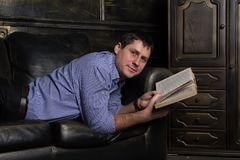 Den unga mannen ligger på soffan och läser en bok royaltyfri bild