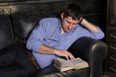Den unga mannen ligger på soffan och läser en bok fotografering för bildbyråer