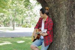 Den unga mannen lutar för att spela den akustiska gitarren på den utomhus- parkera Arkivbilder
