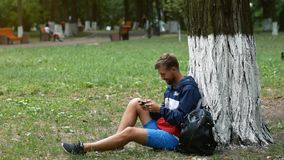 Den unga mannen lutar på ett träd, medan koppla av i, parkerar sittande gräs Studenten finner en minut för att spela mobila lekar stock video