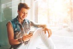 Den unga mannen lyssnar musik med hörlurar och smartphonesammanträde på fönsterbräda royaltyfria bilder