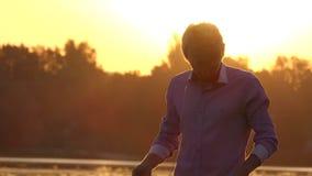 Den unga mannen lyssnar till hans mobil på en sjö på solnedgången i slo-mo stock video