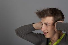 Den unga mannen lyssnar till musik arkivfoton