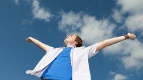 Den unga mannen med armar outstretched mot skyen Arkivbild