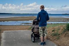 Den unga mannen med behandla som ett barn sittvagnen på stranden royaltyfri foto