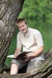 Den unga mannen med boken parkerar in Royaltyfria Bilder