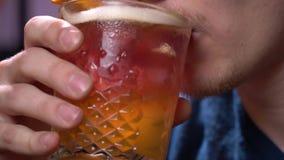 Den unga mannen med borstet tar upp en smutt av ölet, slut lager videofilmer