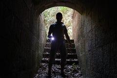Den unga mannen med en ficklampa skriver in stentunnelen Arkivfoton