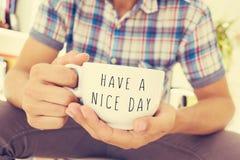 Den unga mannen med en kopp med texten har en trevlig dag Arkivbilder