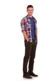 Den unga mannen med händer tucked pockets in Royaltyfri Foto