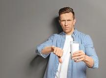 Den unga mannen med hållande exponeringsglas för mejeriallergin av mjölkar royaltyfri bild