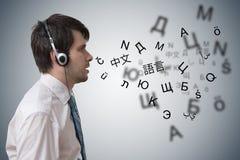 Den unga mannen med hörlurar lär olika utländska språk arkivfoton