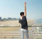 Den unga mannen med handen lyftte att peka upp, stranden i bakgrund Arkivbilder