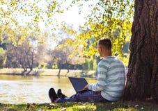 Den unga mannen med hans bärbar datorsammanträde i stad parkerar den utomhus- near sjön Royaltyfria Bilder