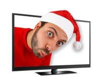 Den unga mannen med hatten av Santa Claus kommer ut från TV:N Arkivfoto