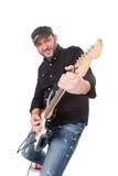 Den unga mannen med hatten och skägget spelar på den elektriska gitarren med entusiasm Isolerat på vit Fotografering för Bildbyråer