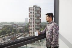 Den unga mannen med kaffe rånar att se ut till och med fönster hemma Arkivbild