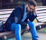 Den unga mannen med ledset ansiktsuttryck som sitter på en bänk i, parkerar Kontorsarbetaren förlorade hans jobb Mellersta åldrig arkivfoto