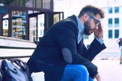 Den unga mannen med ledset ansiktsuttryck som sitter på en bänk i, parkerar Kontorsarbetaren förlorade hans jobb Mellersta åldrig arkivfoton