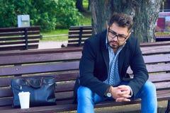 Den unga mannen med ledset ansiktsuttryck som sitter på en bänk i, parkerar Kontorsarbetaren förlorade hans jobb Mellersta åldrig royaltyfria foton