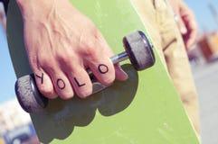 Den unga mannen med ordet yolo, for du bor endast en gång, tatuerat Fotografering för Bildbyråer