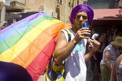 Den unga mannen med regnbågeflaggan på stolthet ståtar TA Arkivbild
