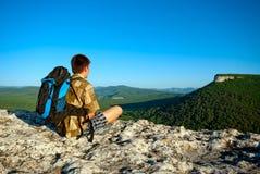 Den unga mannen med ryggsäck sitter Arkivfoto