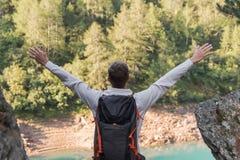 Den unga mannen med ryggsäcken och armar lyftte att tycka om frihet i bergen under en solig dag royaltyfria bilder