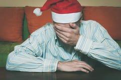 Den unga mannen med den Santa Claus hatträkningen hans framsida med hans händer som känner sig ensamma och ledsna för nytt år och Royaltyfri Bild