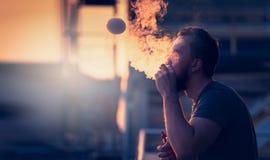 Den unga mannen med skägget på oskarp bakgrundssolnedgånghimmel som gör såpbubblor, röker inom med hjälpmedlet av vape Royaltyfria Bilder