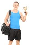 Den unga mannen med sportar hänger löst och en trofé Arkivbild