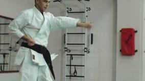 Den unga mannen med den tränga sig in kroppen, utbildande kampsporter Goju-Ryu Karate-gör arkivfilmer
