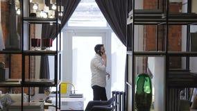 Den unga mannen meddelar genom att använda mobiltelefonen i kontor för tegelstenvägg arkivfilmer