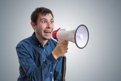 Den unga mannen meddelar nyheterna med megafonen Royaltyfri Fotografi