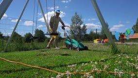Den unga mannen mejar gräsmattan med i barnlekplatsen Gimbalrörelse arkivfilmer